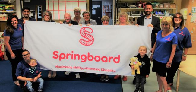 The Springboard team, with two children they help, posing with their brand new logo which was designed by Chippenham design agency Milk and Tweed