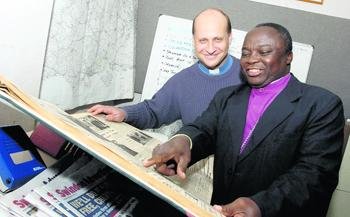 This Is Wiltshire: The Rt Rev Julius Kalu with an archive copy of the Advertiser watched by the  Rev Simon Stevenette