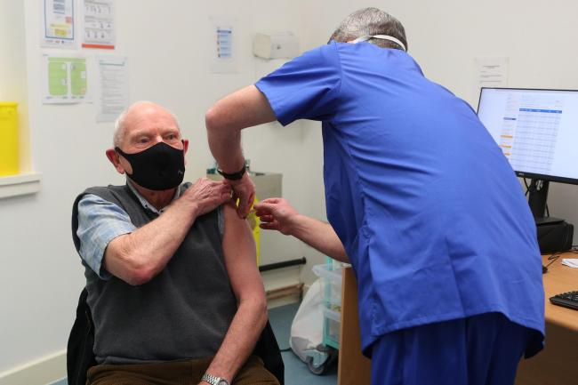 Pharmacist Andrew Hodgson administers a dose of the coronavirus vaccine to Robert Salt, 82, at Andrews Pharmacy in Macclesfield, Cheshire