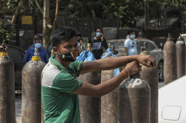 Family members of Covid-19 patients wait in queue to refill their oxygen cylinders in New Delhi, India. Picture: AP