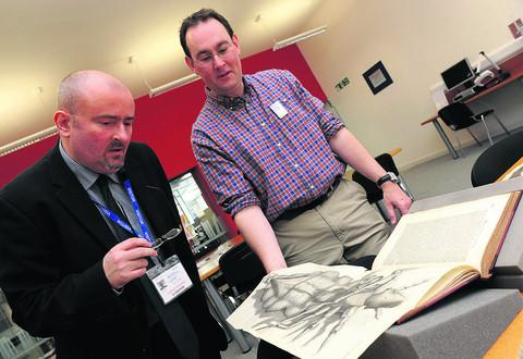 Barrie Hudson and assistant librarian John Underwood examine an illustration of a headlouse