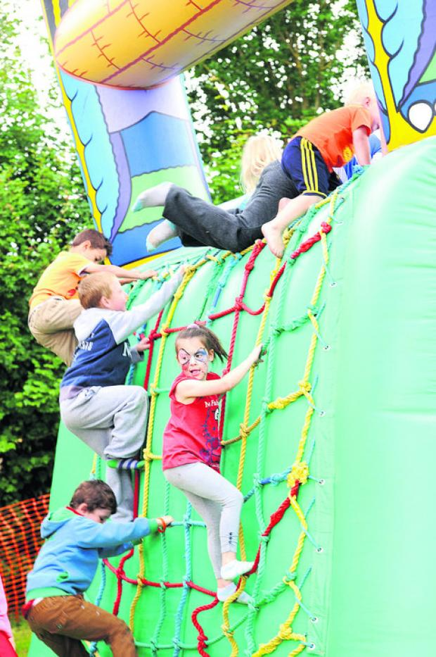 This Is Wiltshire: Children scale the walls of the bouncy castle