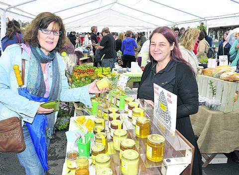 Michelle Luck makes a purchase from Fee Robinson's honey stall