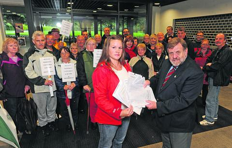 This Is Wiltshire: Rebecca Millard hands the petition to Councillor Graham Payne, chairman of Trowbridge Area Board, who supports the Innox plans