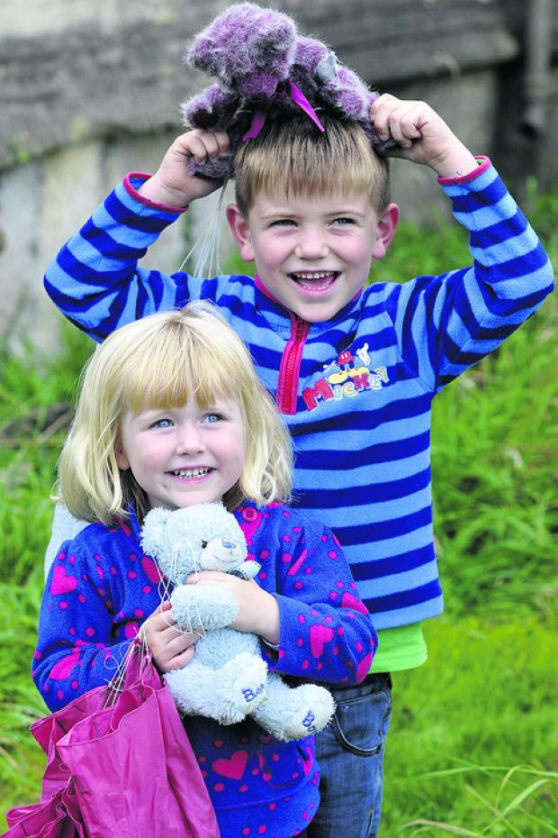This Is Wiltshire: Oliver and Maise Berry congratulate their bears for parachuting down from St Bartholomew's Church tower