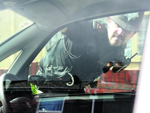 This Is Wiltshire: PC Dave Johnson inspects cars after the vehicle break-ins in Hunters Grove