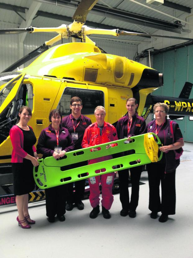 This Is Wiltshire: Staff from Sainsbury's in Calne present a Combi Carrier to Claire Kelly of the Wiltshire Air Ambulance and paramedic Steve Riddle after the store raised funds from customer donations and charity sales