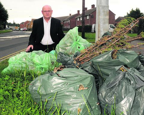 Labour leader Jim Grant with green rubbish which has not been collected