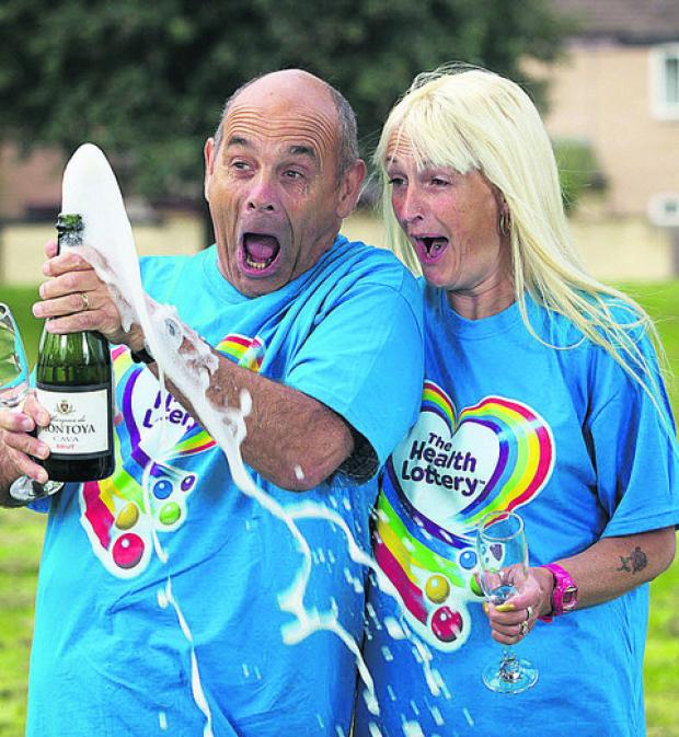 Peter Chapman cracks open a bottle of bubbly with his wife Karen to celebrate his £200,000 Health Lottery win