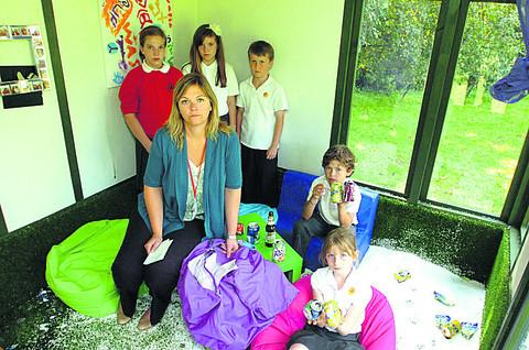 This Is Wiltshire: Acting headteacher Becky Wilson with pupils in the summerhouse that was vandalised during the summer holidays