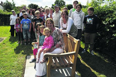 This Is Wiltshire: Mother Jenny Wills, seated, and fundraising organiser Lynsey Doel, centre right, unveil the bench with family, friends and parish councillors