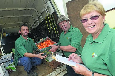This Is Wiltshire: Adrian Topp and Cary and Carol Thompson check over produce for their delivery service after the closure of the Village Veg shop. Below, the Thompsons at work