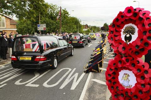 This Is Wiltshire: Mourners pay tribute as the three hearses pass through Carterton in Oxfordshire