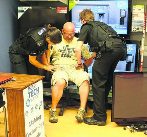 This Is Wiltshire: Mr Rawlinson being removed from the Ocotal Way store by police after his four-hour protest