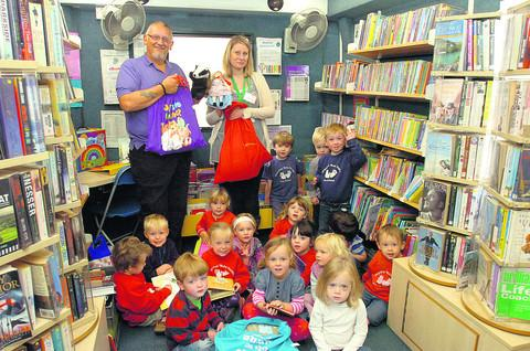 This Is Wiltshire: Library manager Steve Taylor and Rachael Page, from Malmesbury Children's Centre, with youngsters and their Storysacks