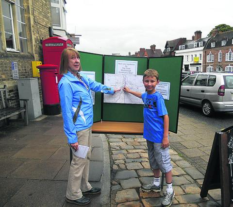 This Is Wiltshire: Shirley Pryor from Transition Marlborough and helper Charlie Wakeham, 11, with a map at the library of all the homes signed up for the town's first community sale