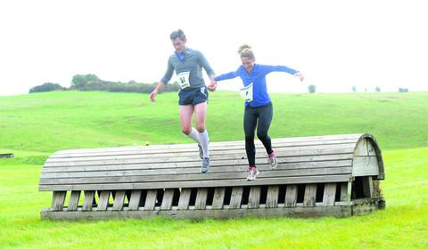 This Is Wiltshire: JUMP TO IT: David Armitage and Sarah Armitage, both from Marlborough, take part in the Horseless Steeplechase in aid of Wiltshire Air Ambulance and the Greatwood charity
