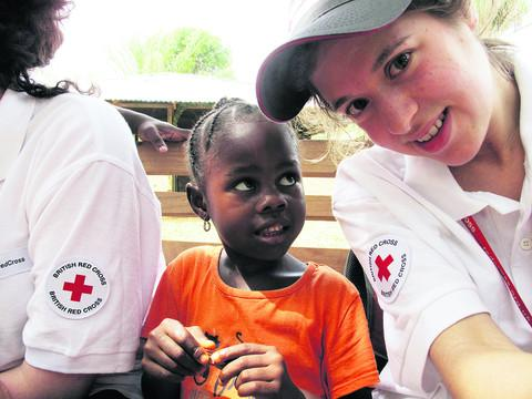 This Is Wiltshire: Anna Hirsch-Holland with a little local girl during a trip to Liberia with the Red Cross