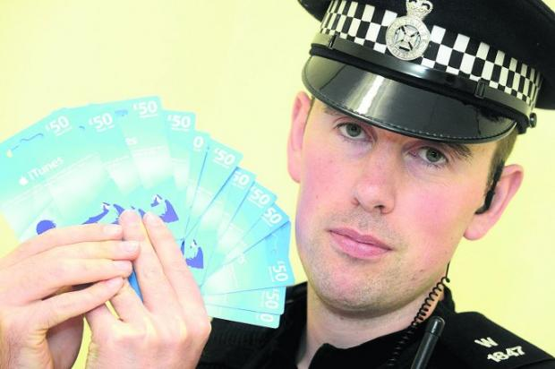 This Is Wiltshire: BLACK MARKET PC Frank Keys with the stolen iTunes vouchers found during a raid Picture: THOMAS KELSEY