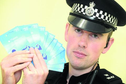 This Is Wiltshire: PC Frank Keys with the stolen iTunes vouchers found during a raid