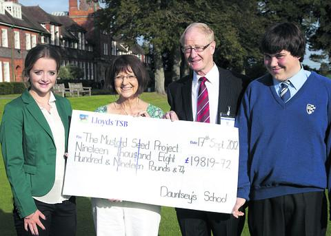 This Is Wiltshire: Charity founders Rita and Geoff Fowler receive the funds raised from Dauntsey's School pupils Jenna Richmond and Sam Jackson