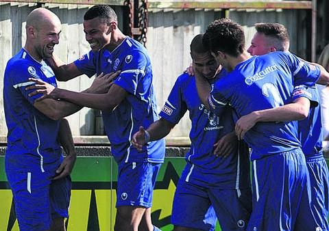 This Is Wiltshire: Tyrone Mings (second from left) congratulates Alan Griffin in Saturday's win over Swindon Supermarine