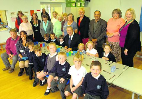 This Is Wiltshire: Coun John Thomson, centre, with residents and pupils, at the launch of the lunch club