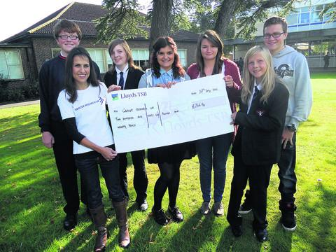 This Is Wiltshire: Maria Gomez, second left, of Cancer Research, receives the cheque from pupils, from left, Freddie Powell, Iona Johnstone, Sophie Roberts, Joanne Wicks, Caitlin Johnstone, Richard Horton
