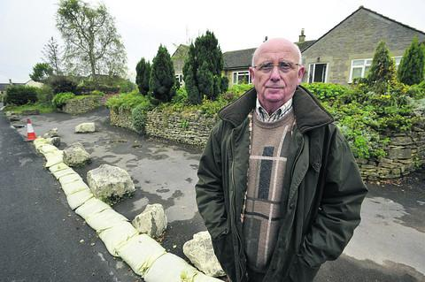 This Is Wiltshire: FED UP: Mike Denning outside his home in Colerne where road repairs have led to flooding