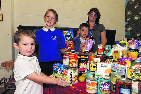 This Is Wiltshire: Pupils Alfie, Charley and Alex sort through the tins and foods with Helen Clarke at the Staverton School harvest festival
