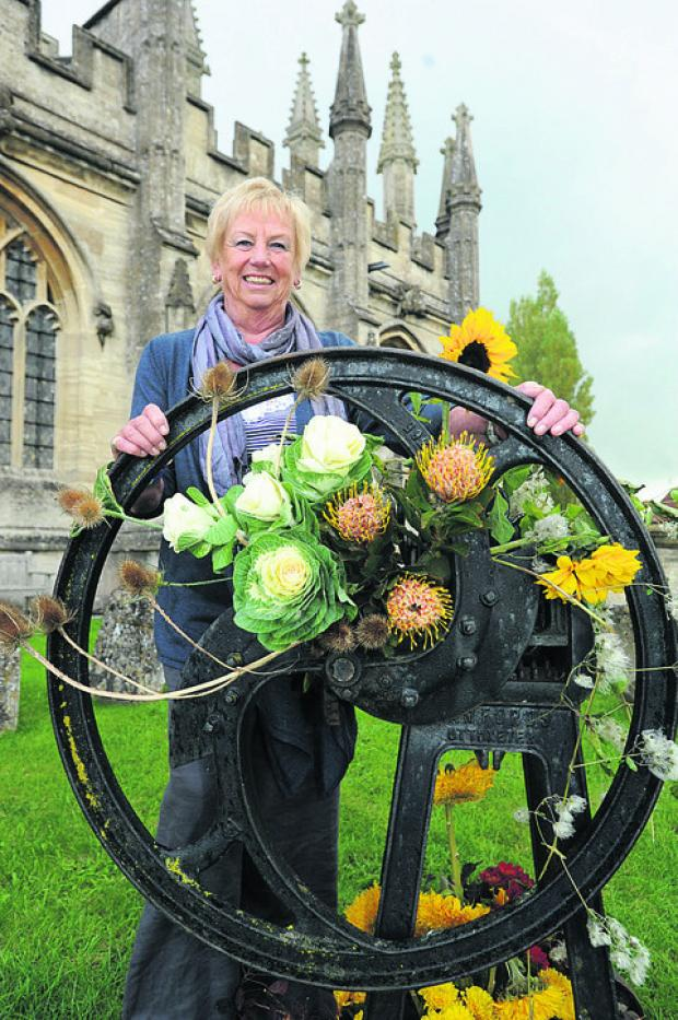 This Is Wiltshire: Head of flowers Joan Campbell with a floral display around a butter churn outside the church