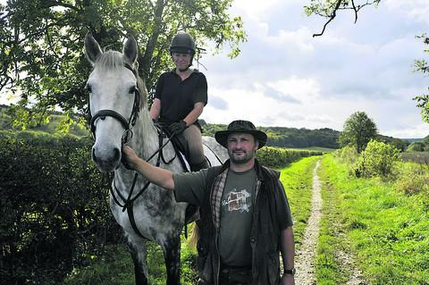 This Is Wiltshire: Adrian Miles of the White Horse Equestrian Centre with rider Maddy Bias and Rose, on one of the routes used by bikers