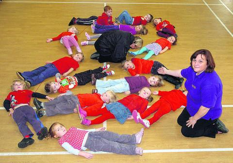 This Is Wiltshire: Playgroup leader Ali Slade and children form a poppy to get ready for Remembrance Day