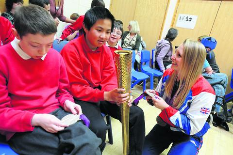 Stephanie Millward shows her medals and torch to St Nicholas School pupils Matthew and Ben