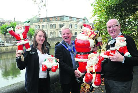 This Is Wiltshire: Santas painted over the first weekend of October will be out in Bradford on Avon for the town's Christmas celebrations. Yaiza Read, Mayor John Potter and Andrew Wright inspect the