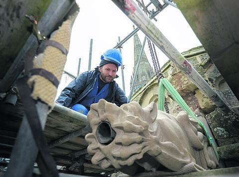 This Is Wiltshire: Matt Barton gently lowers the gargoyle in place