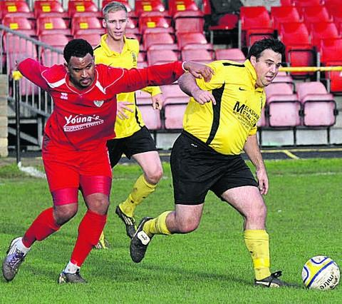 This Is Wiltshire: Melksham Town's Dave Macey (right) gets on the ball against Odd Down on Saturday.