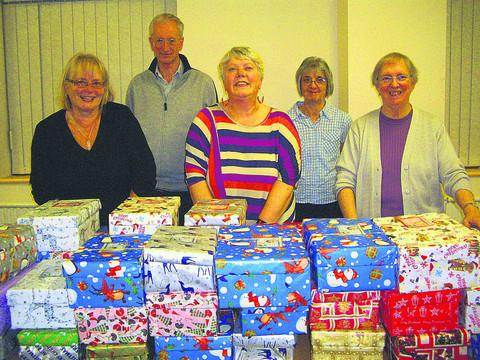 This Is Wiltshire: Members of Westbury United Reformed Church, from left, Maggie Skyrme, Roger Rushmere, Hilary Herring, Janet Rushmere and Kathryn Cundick make an early start on filling 40 shoe boxes for the Operation Christmas Child campaign