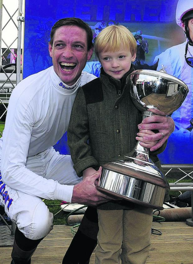 This Is Wiltshire: Richard Hughes receives the Flat jockey's championship title, with son Harvey