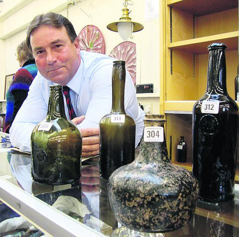 Auctioneer Gordon Brockman with some of the bottles that went under hammer