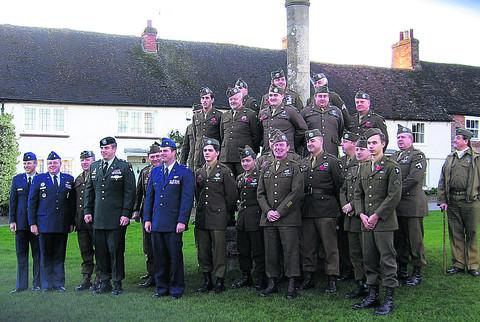 This Is Wiltshire: Members of the Screaming Eagles on The Green, Aldbourne, with Lt Col Mark Houston (in green), a serving officer in the 506 Parachute Infantry Regiment, and three USAF officers following the Remembrance Day service in St Michael's Church