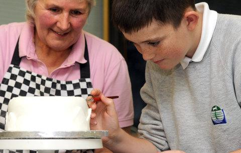 Carole Stafford, of Sugar Celebration, showing Bradon Forest pupil Kyle Wallace, how to decorate a Christmas cake