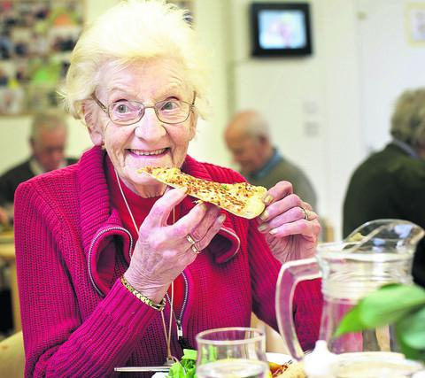 Doreen Fitzhugh tucks into pizza donated by Domino's at the Alzheimer's Support centre in Sidmouth Street