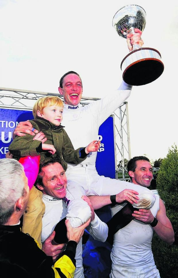 This Is Wiltshire: Richard Hughes celebrates his title win with son Harvey at Doncaster on Saturday