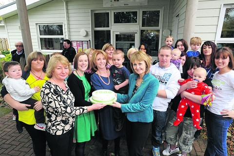 Jane Asher slices into a cake with some staff and parents