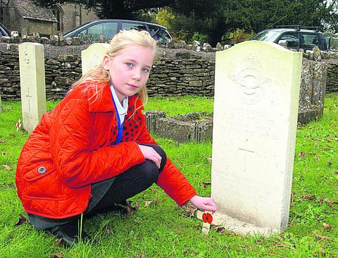 This Is Wiltshire: Year six pupil Amelie lays a poppy cross at the grave of Pilot Officer AB Lapointe
