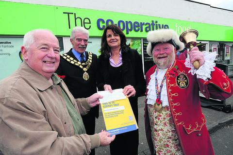 This Is Wiltshire: Henry Leigh of the Co-operative hands a cheque to Eva Ashmore of Help Counselling, as mayor John Knight and Town Crier Trevor Heeks join the event at the shop in Seymou