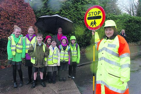 This Is Wiltshire: Lollipop lady Emma Dexter helps head teacher Sarah Brewis and children cross the road on the new crossing