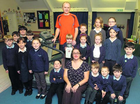 This Is Wiltshire: Andrew Hughes with his daughter Carys and Broad Hinton School pupils and head teacher Elizabeth Floyd