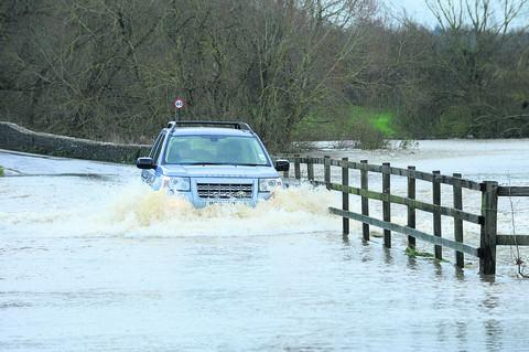 A car makes its way through flooded lanes at Lacock